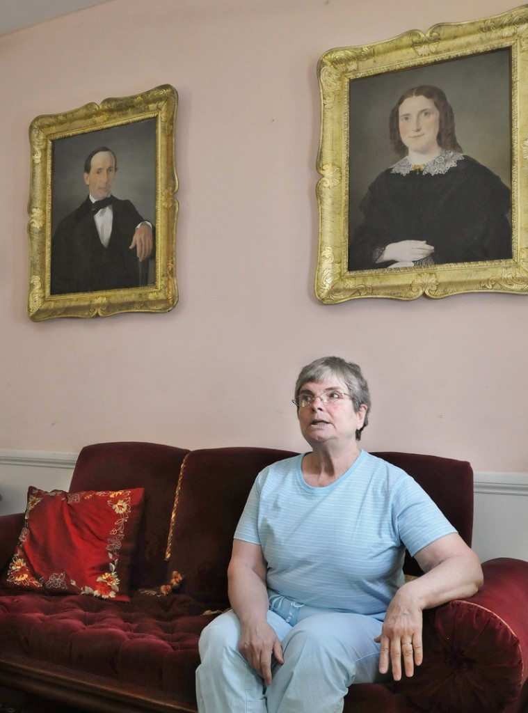 Merry Chapin sits beneath paintings of her great-grandparents, Capt. Reuben and Hannah Blanchard Merrill, at her historic house in Yarmouth, now headquarters for Maine Preservation.