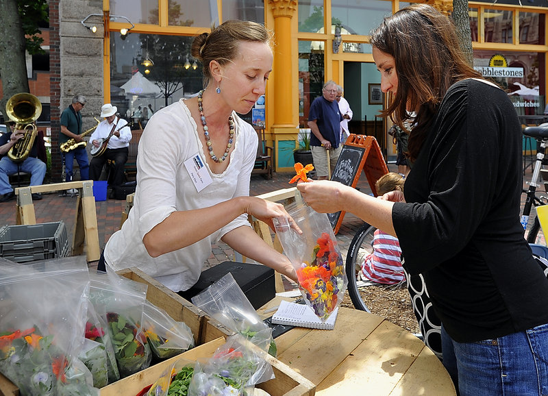 Stephanie Hedlund of Clara Burke Kitchen, right, buys greens and edible flowers from Mary Ellen Chad of Green Spark Farm in Cape Elizabeth.