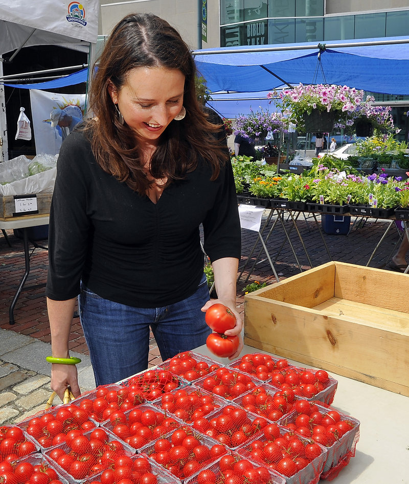 Stephanie Hedlund shops for tomatoes at the Olivia's Garden table at the Portland Farmers Market in Monument Square.