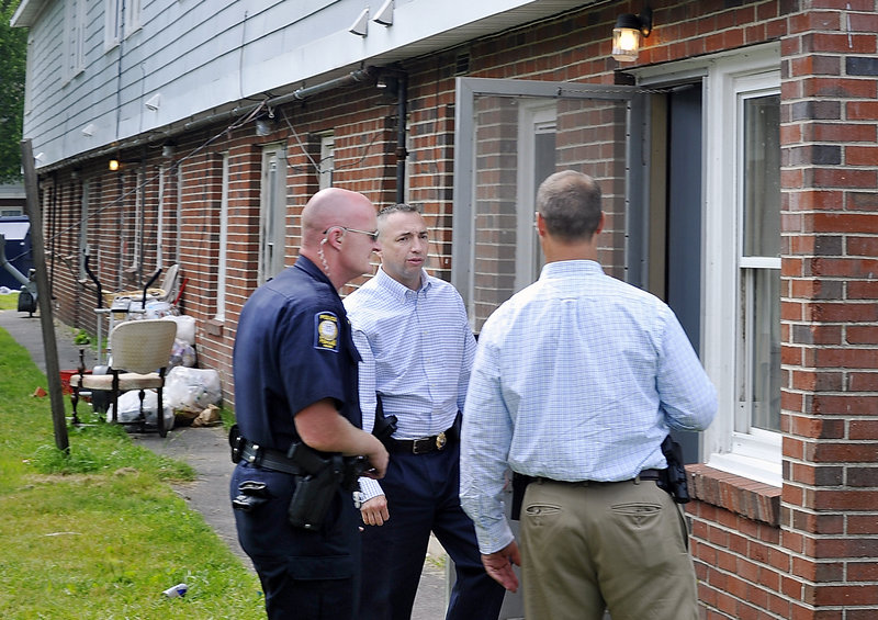 Assistant Police Chief Michael Sauschuck, center, talks with Officer Mark Kezal, left, and Lt. Gary Rogers, head of the Special Reaction Team that responded to the Riverton Apartments on Friday.