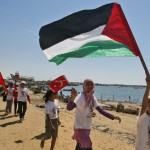 Palestinian children fly Palestinian and Turkish flags in the port of Gaza City on Saturday to show their support for the flotilla that is attempting to reach the Gaza Strip.
