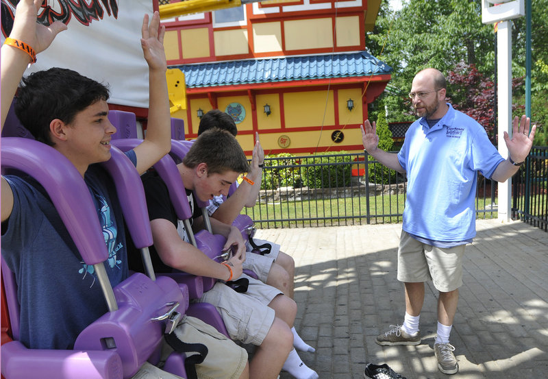 Reporter Ray Routhier asks riders to lift their arms so he can see that they are securely strapped into the Dragon's Descent ride at Funtown Splashtown USA.