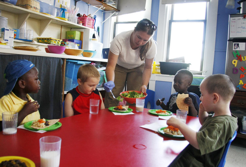 Kayla Landry, a teacher at the Youth & Family Outreach daycare center in Portland, serves lunch to her young charges.