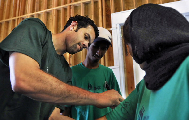Jordan Farmar, signing a shirt for Shifaimran, a camper, not only attended Seeds of Peace for the third year, but has conducted weeklong basketball camps in Israel for Israeli and Palestinian children.