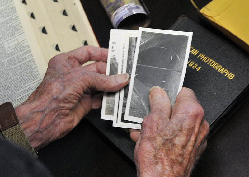 Morse holds photos from his time of military service during World War II.