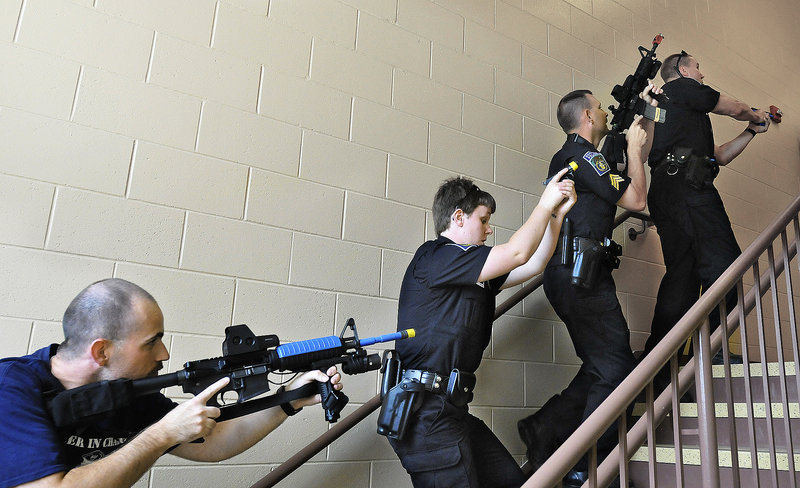Police officers from the Gorham and Westbrook police departments advance up a stairway during a training session on handling hostage situations Tuesday at the Westbrook Middle School. Officers were engaged in scenarios that became more complex, with harder-to-find shooters and hostages.