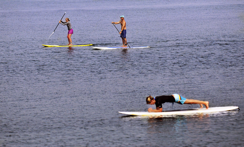 """Rafael Adams and Tonya DiMillo pass a fellow paddle boarder practicing yoga on her board in Kettle Cove. """"You can paddle for hours with no waves,"""" Adams said."""