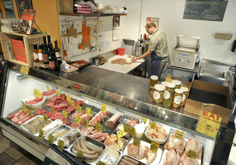 Butcher Jarrod Spangler, of Rosemont Bakery and Market in Portland, cuts meats and makes all sausages by hand. The store is one of 10 in Maine to win a green-grocer certification from the Department of Environmental Protection.
