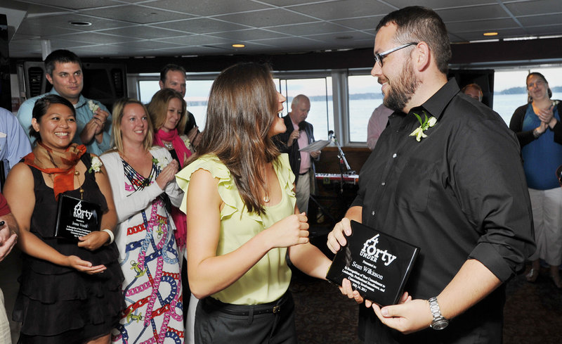 Sean Wilkinson, one of the Forty Under 40 winners, receives his award from Sarah Madeira, administrative assistant to the executive editor of The Portland Press Herald, as other recipients applaud during Thursday night's tour aboard the Bay Mist cruise ship.