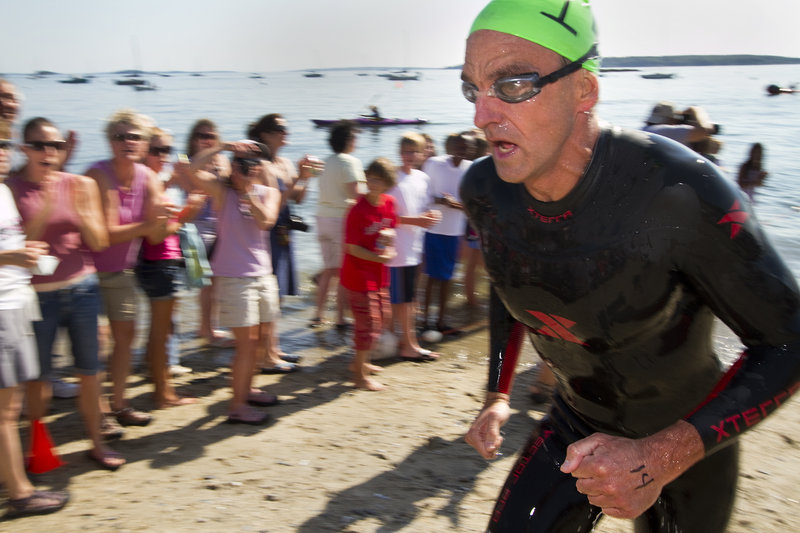 "Scott Yeomans, 47, reaches the beach as the first out of the water to win the Peaks to Portland. ""You have to stay focused on your stroke and keep going,"" he said."