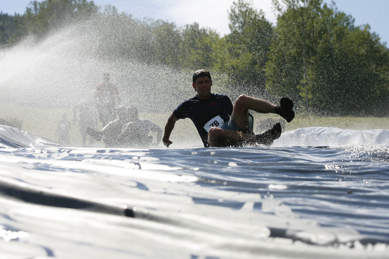 The Slip, Slide & Die obstacle gives competitors a fast ride into a muddy pit.