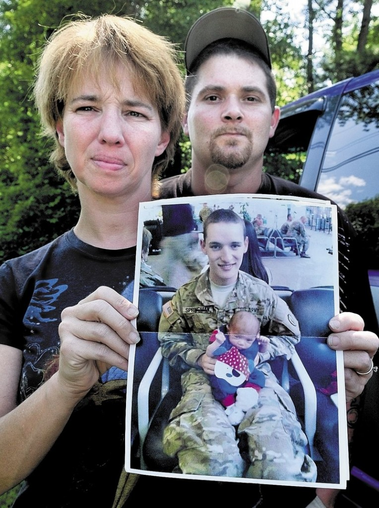 Tina Stratton holds a photograph of her son Pfc. Tyler M. Springmann, who was killed Sunday while serving in Afghanistan. At right is Stratton's husband, Ben Martin.