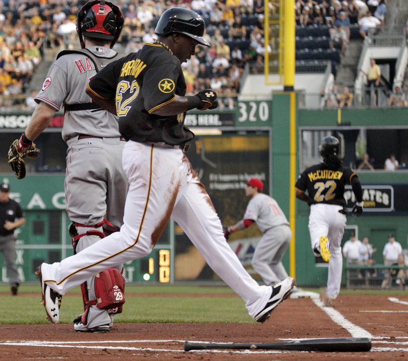 Josh Harrison of the Pirates scores on Andrew McCutchen's grounder Tuesday night in the 1-0 victory against the Reds.