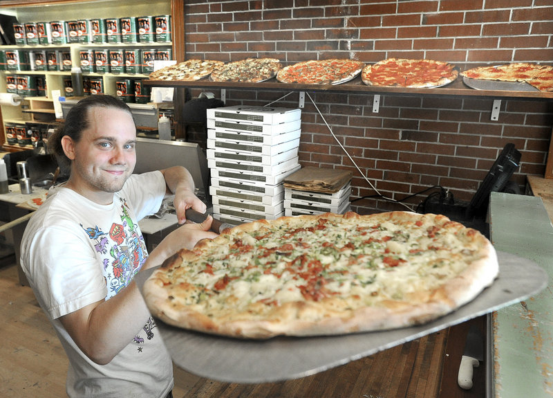 Nemo Burian hoists a freshly baked potato, bacon and scallion pizza at Otto Pizza on Congress Street in Portland, the Readers Choice winner for best pizza.