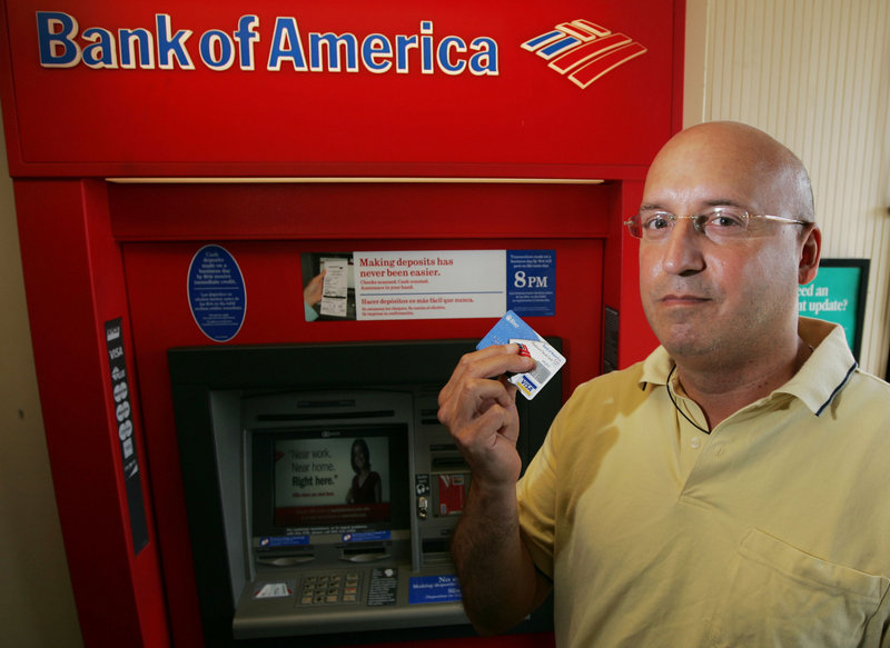Scott Rozman holds up his Bank of America ATM card in Guttenberg, N.J. He says he plans to switch banks because of Bank of America's fees.