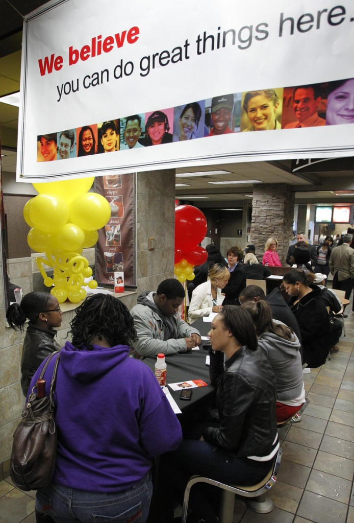 Job seekers fill out applications at a Pittsburgh McDonald's. The company's earnings rose 15 percent in the second quarter.