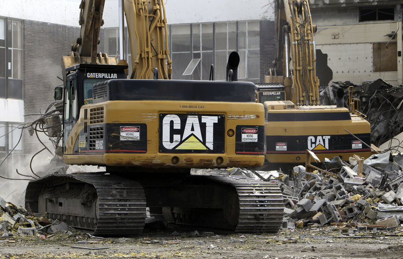 Caterpillar excavators tear down a school in Detroit. Demand for heavy equipment boosted quarterly profits 44 percent.
