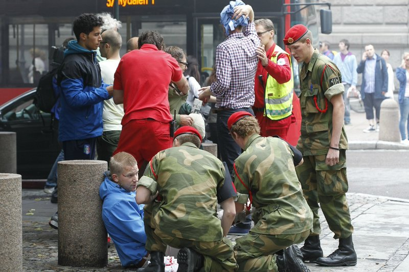 Wounded people are treated in the street in Oslo on Friday after an explosion tore open buildings including the Norwegian prime minister's office. A second related attack –a rampage at a youth summer camp – claimed more victims, for a combined death toll of at least 87.