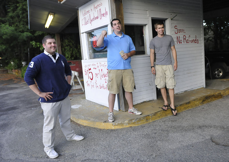 """Ry Russell, Tyler Wells and Patric Brophy, University of Southern Maine marketing students and managers of the Saco Drive-In, talk with customers at the entrance Friday. """"You can't beat it as a family coming here,"""" Wells said."""