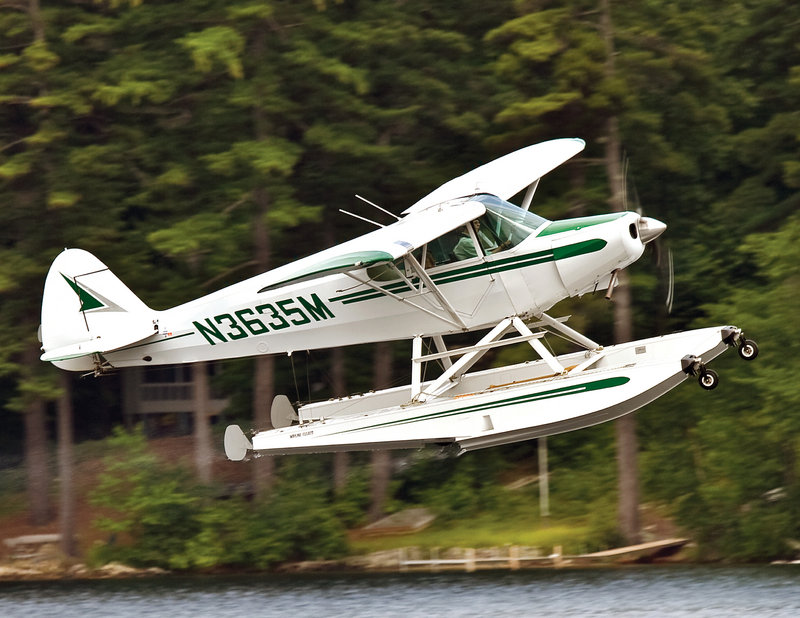 It is common to see seaplanes above the Lakes Region at this time of year. Here, Mary Build, who earned her wings in 1991, takes off with her grandkids in a Piper Cub.
