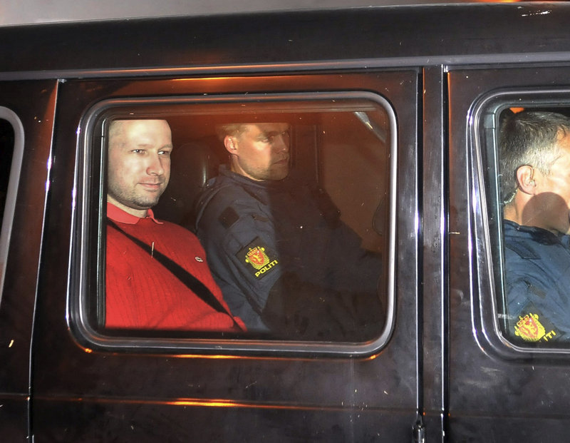 Attack suspect Anders Behring Breivik, left, who is wearing a uniform, sits in an armored police vehicle at a courthouse Monday in Oslo.