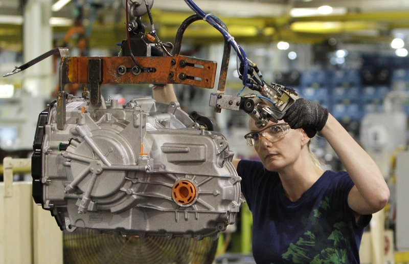 Cheryl Simpson moves a transmission from the assembly line to a pallet at the Ford Van Dyke plant in Sterling Heights, Mich.