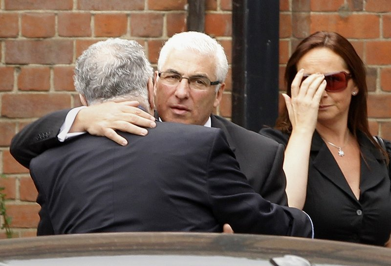 Mitch Winehouse, center, the father of deceased singer Amy Winehouse, is consoled as he arrives at a crematorium in north London on Tuesday.