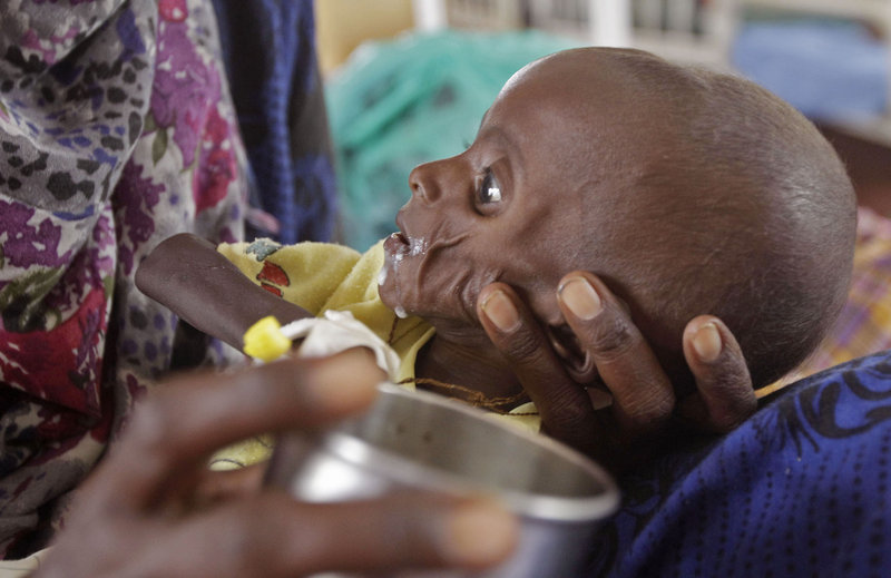 Mihag Gedi Farah, a 7-month-old Somali child who is severely underweight, is fed by his mother as he lies in a field hospital of the International Rescue Committee in the town of Dadaab, Kenya, on Tuesday. Tens of thousands of Somalis are fleeing to Kenya and Ethiopia, hoping to find aid in refugee camps.