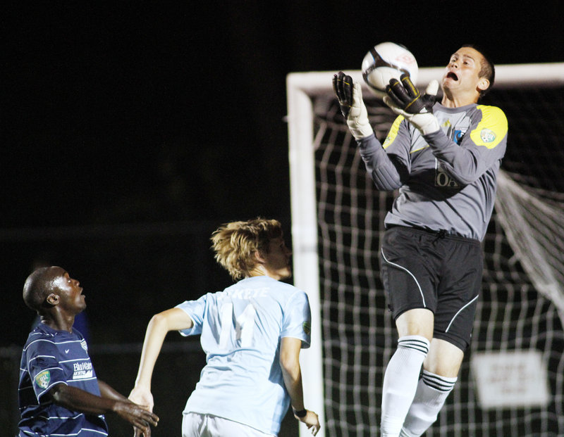 Portland goalie Matt Williams makes a save as teammate Brian Fekete, center, holds off a New Hampshire player Tuesday night during a Premier Development League playoff game at Deering High. New Hampshire advanced with a 1-0 victory.