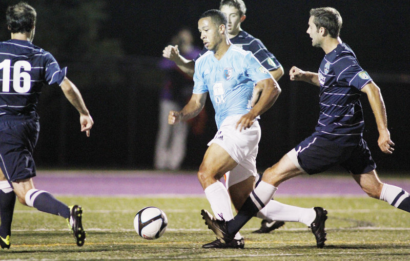 Charlie Rugg of the Portland Phoenix tries to dribble his way through a ring of New Hampshire defenders Tuesday night at Deering High's Memorial Field. The Phantoms advanced in the PDL playoffs with a 1-0 victory Monday.