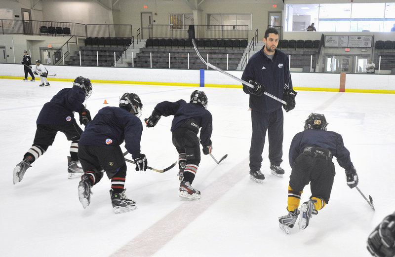 Matt Duffy, a former University of Maine hockey player from Windham, leads a group of young players through a drill Wednesday during a summer hockey camp at Falmouth Ice Center. Twelve current and former UMaine players are working at the camp this week.