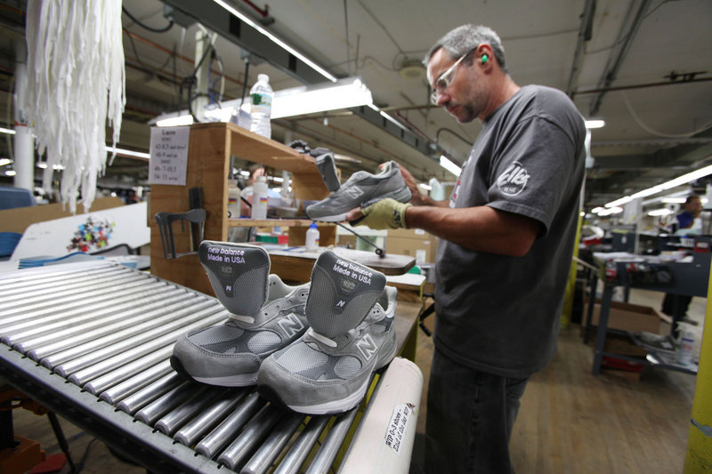 Kirby Knox inspects a shoe at the New Balance factory in Norridgewock. Knowing that the company could make far more money if, like Nike and Adidas, it shifted most of its jobs to low-wage countries, Maine workers try to make up the difference through efficiency.