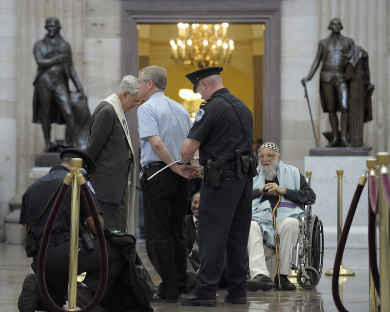 Rabbi Arthur Waskow, seated, waits to be arrested by Capitol Police in the Rotunda of Capitol Hill in Washington on Thursday. Rep. Chellie Pingree, D-Maine, defended members of the group of civic and religious leaders who were arrested after protesting proposed budget cuts associated with debt ceiling negotiations.