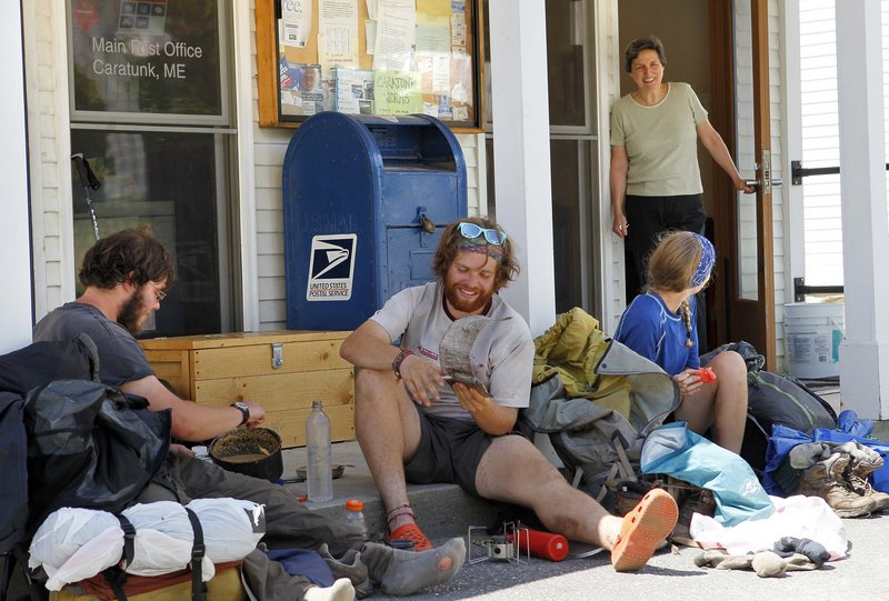 Postmistress Maie Beane chats with Appalachian Trail thru-hikers, from left, Greg Brown and David Hyman of Pleasantville, N.Y., and Madelyn Hoagland-Hanson of Philadelphia, as they eat lunch outside the post office in Caratunk on Thursday.