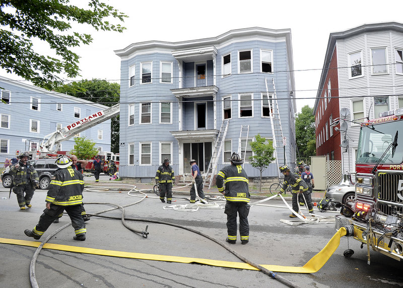 Portland firefighters clean up after an apartment house fire at 123 Sherman St. in Portland on Friday afternoon forced residents to flee, with some dropping children from windows to neighbors below. No injuries were reported.