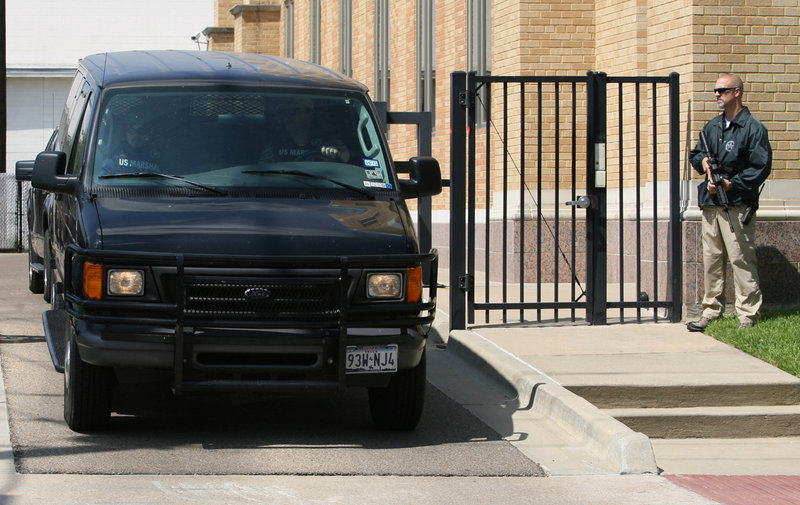 A U.S. marshal stands guard at a security gate as a black van carrying AWOL soldier Pfc. Naser Abdo leaves a U.S. federal courthouse Friday in Waco, Texas. Abdo is accused of plotting an attack at a restaurant frequented by soldiers from Fort Hood.