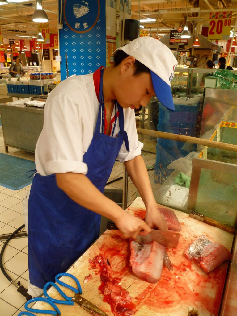Gui Jin Yu cuts freshly killed carp into fillets at a supermarket in Shanghai, China. Throughout China, shoppers prefer to buy freshwater fish that has been killed minutes before, and they eat it the same day.
