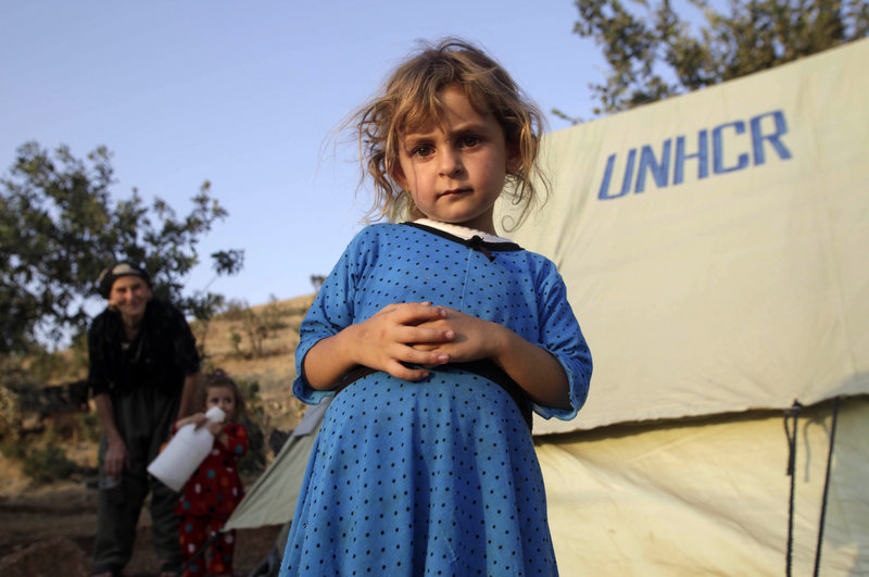 Solin Doher, 5, stands near her family's tent this week at a camp for people displaced by fighting near Sone village in northern Iraq. A report on Iraq says the U.S. military is glossing over the country's instability.
