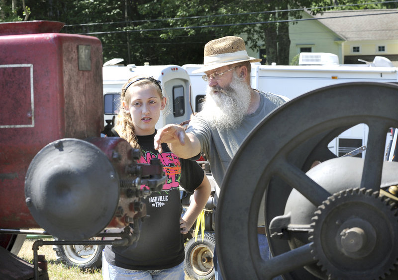 Ted Greene discusses an antique engine with his granddaughter, 14-year-old Zoe Greene of Sebago.