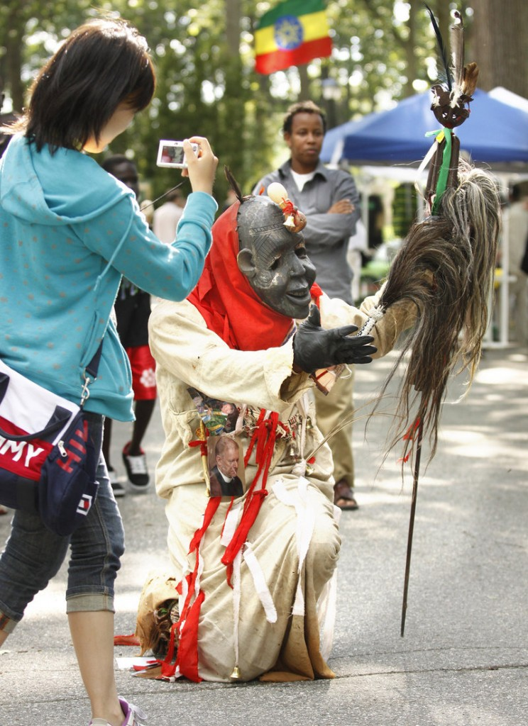 A woman photographs Chief Oscar Mokeme of the Museum of African Culture as he dances at the Festival of Nations in Deering Oaks park in Portland on Saturday.