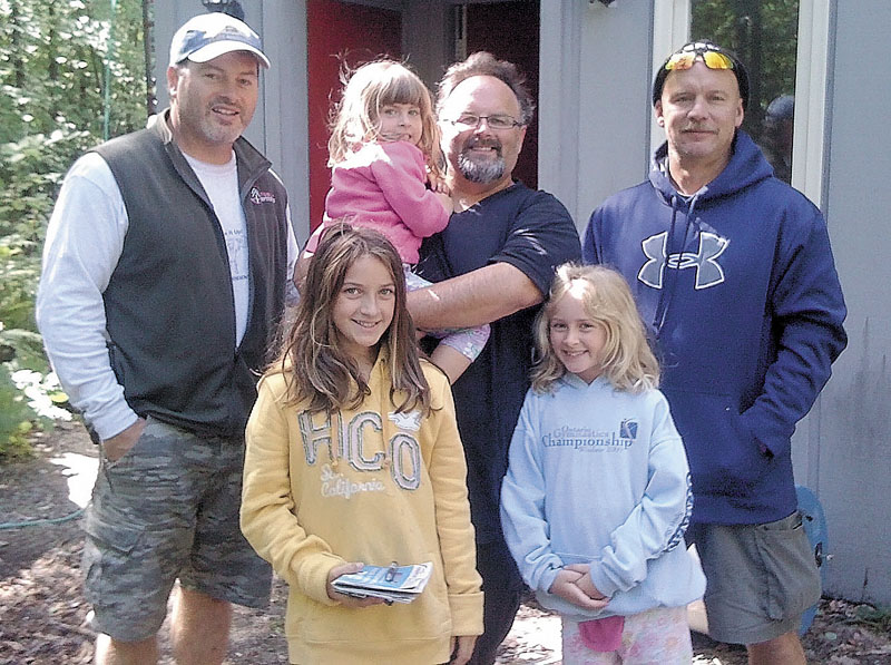 KINDNESS OF STRANGERS: Robert Dupre, left, opened his home in Carrabassett Valley to a family of strangers who were caught by Tropical Storm Irene Sunday. With Dupre is Rob Roberts, holding his daughter Aislinn, and other daughters Fiona, left, and Cait. Also shown is Dupre's friend, Mike McKeon, who also spent the night with the group.