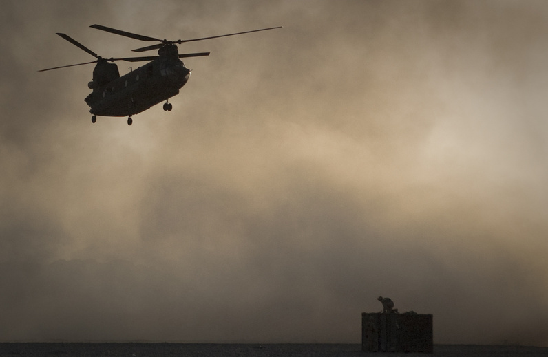 A Marine perched on a container, tries to take cover from the dust as a Chinook helicopter arrives to pick up supplies at Forward Operating Base Edi in the Helmand province of southern Afghanistan, in this June 9 file photo. Afghan President Hamid Karzai said 31 U.S. special forces and seven Afghan soldiers were killed when a helicopter, similar to the one shown, crashed in eastern Wardak province late Friday.