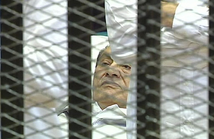 This video image taken from Egyptian State Television shows 83-year-old former Egyptian president Hosni Mubarak lying on a hospital bed flanked by his two sons Gamal and Alaa, inside a cage of mesh and iron bars in a Cairo courtroom today.