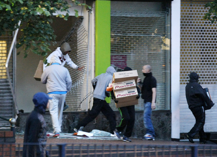 Looters take electrical goods after breaking into a store during the second night of civil disturbances in central Birmingham, England, on Tuesday.