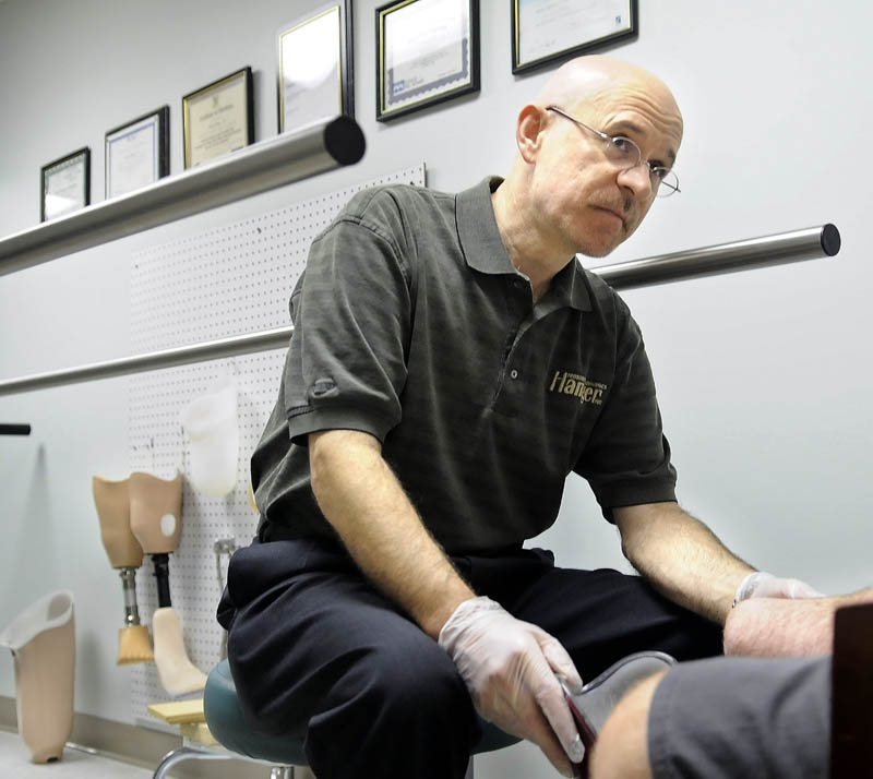 WORKS WITH THE INJURED: Kevin Carroll, left, assesses the amputated right leg of Pat Brown, of Pittsfield, Wednesday during a clinic at Hanger Prosthetics and Orthotics in Augusta. Brown lost his leg in a parachute accident.