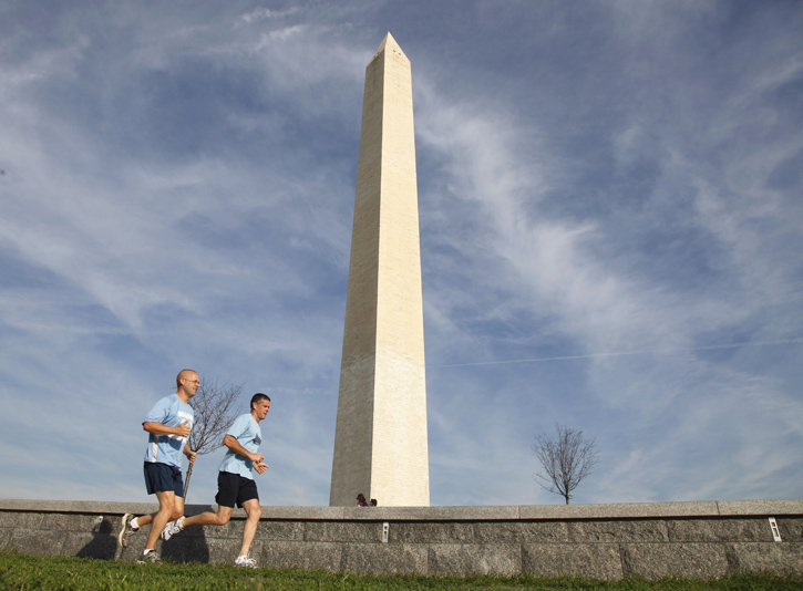 Joggers today run past the Washington Monument, which remains closed after a crack was discovered at the top of the towering white obelisk on The National Mall.