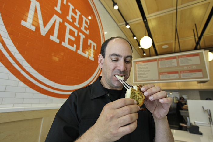 In this photo taken Aug. 25, 2011, Jonathan Kaplan bites into a melt called the Italian Job made with fontina and provolone cheese on garlic bread at The Melt in San Francisco.