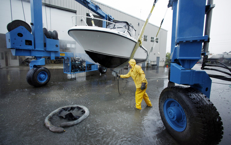 Peter Gavett pressure washes the hull of a pleasure boat he hauled out of the water at Brewer Marine as a precaution before the arrival of Hurricane Irene today in Freeport.