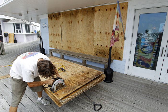 Jeremy Pickett cuts boards to protect the windows of a store in Cape Hatteras.