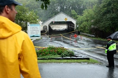 Emergency crews keep people at a safe distance as water from the Ottauquechee River overcomes the Quechee Covered Bridge yesterday. Rising water caused evacuations from the apartment buildings along the Green, flooded the interior of Simon Pearce and eventually swept the bridge away.